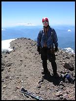 Climb of Mount Rainier: Daniel on the summit with Mount Adams in the background