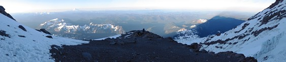 Mount Rainier climb: panorama with Mount Adams and Mount St Helens in the background; Camp Hazard with Kira and Dustin and Mount Rainier's shadow in the foreground
